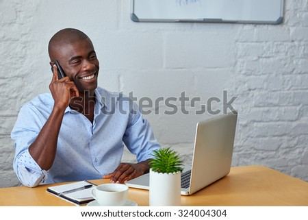 professional african black man talking on mobile cell phone to clients in office with laptop computer