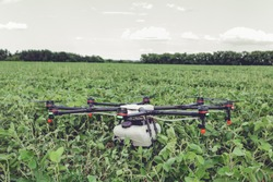 Professional agriculture drone stands on the ground green field. Octocopter flight preparation