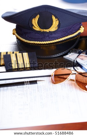 Professional airline pilot hat and id holder with epaulets and sun glasses laying on log book and flight plan.