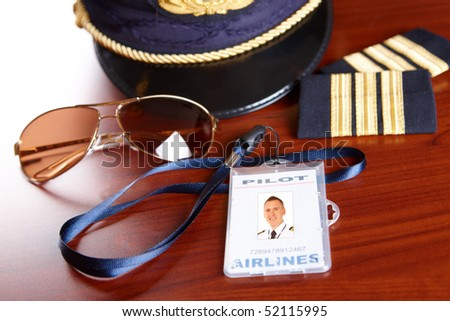 Professional airline pilot hat and id holder with epaulets and sun glasses laying on table