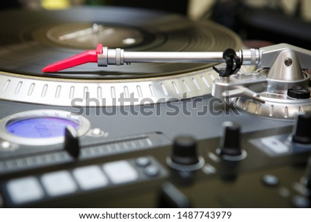 Professional analog dj turntable player with red spherical needle playing old record with music on party in night club.Stage audio equipment for disc jockey  to play musical set