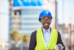Professional architect in hard hat looking at camera. Confident architect standing at construction site. Portrait of African American Engineer at a construction worksite. Looking at camera.