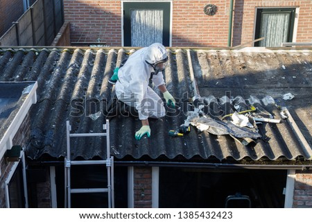 Professional asbestos removal. Men in protective suits are removing asbestos cement corrugated roofing