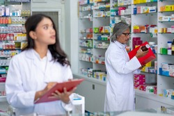 Professional Asian male and female Pharmacist checking medicines and health care product inventory stock on shelf at hospital pharmacy or drugstore. Medical, pharmaceutical and healthcare concept.