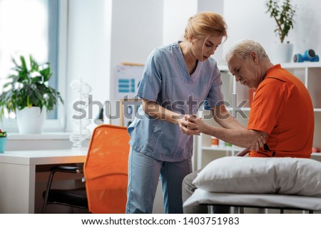Professional assistance. Professional female nurse standing above her patients bed while holding his hand