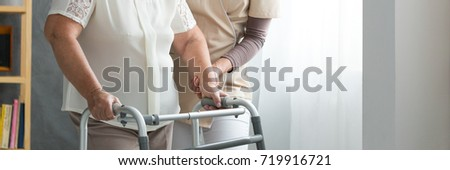 Professional assistant supporting elderly woman in white shirt using walker in living room