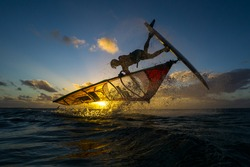 professional athlete doing incredible trick at windsurfing on the background of a picturesque sunset and spray. Mauritius, Indian Ocean