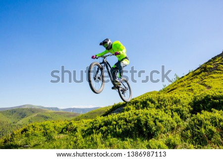 Professional athlete jumps high on a mountain bike. Picture with background of blue sky. Sunny summer day