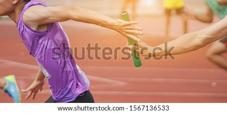 Photo of  Professional Athlete passing a baton to the partner against race on racetrack.selective focus.