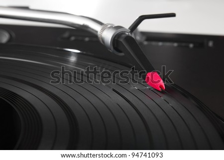 Professional audio equipment for disc jockey - turntable record player with high-class spherical needle. Closeup shot of tonearm on the vinyl disc.