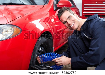 Professional auto mechanic changing tire in auto repair for Garage service professionals