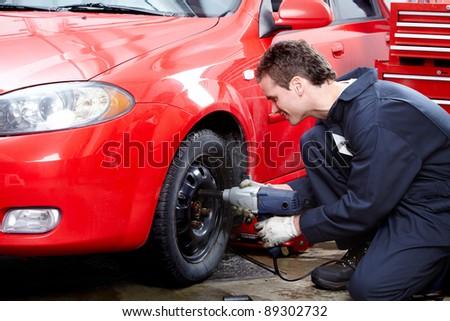 Professional auto mechanic v in auto repair shop. Garage.