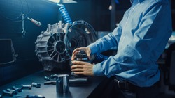 Professional Automotive Engineer in Glasses is Working on Transmission Gears in a High Tech Innovative Laboratory with a Computer Screens.