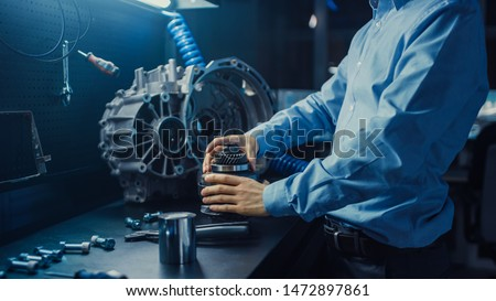 Professional Automotive Engineer in Glasses is Working on Transmission Gears in a High Tech Innovative Laboratory with a Computer Screens. #1472897861