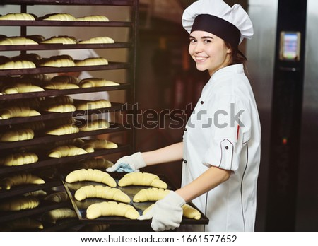 professional Baker - a young attractive woman in a white chef's jacket and cap smiles and holds a tray of raw croissants against the background of a bakery or bread factory. Foto d'archivio ©