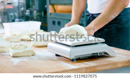 Professional baker divides the dough into portions and weights them. Process of making bread at bakery commercial kitchen.