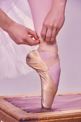 Professional ballerina putting on her ballet shoes.on the  wooden chair on a pink background. feet close-up