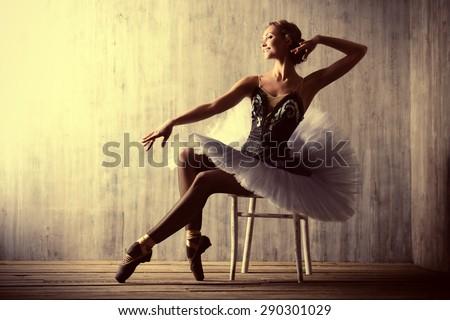 Professional ballet dancer posing at studio over grunge background. Art concept.