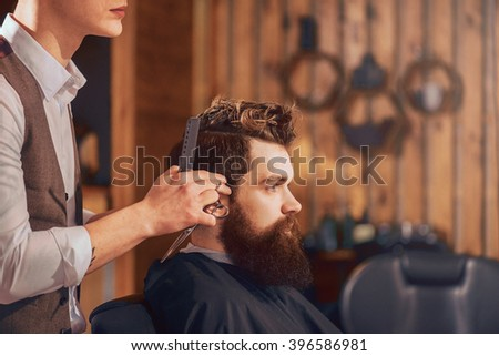 Professional barber styling hair of his client #396586981