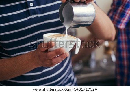 Professional barista and bartender pouring latte foam over coffee, espresso and creating a perfect cappuccino