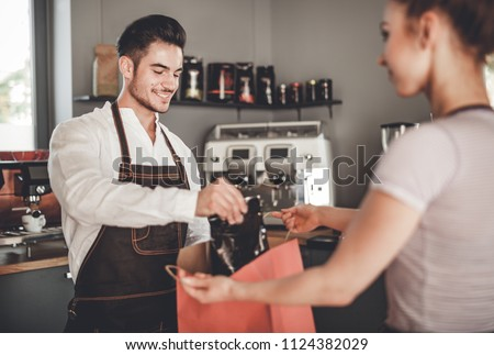Professional barista giving shopping bag to customer at coffee shop, cafe small business Photo stock ©