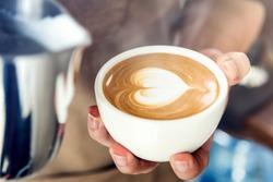 Professional barista holding coffee cup making beautiful heart shape latte art