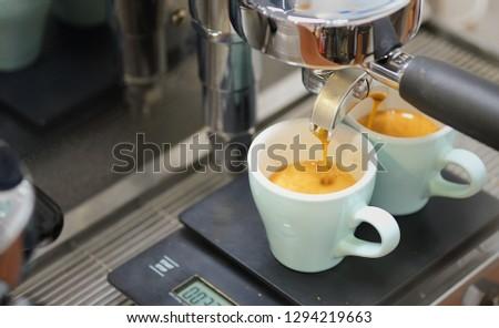 Professional barista making espresso with espresso machine. Espresso cup on black scale #1294219663
