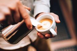Professional barista pouring latte foame over coffee, espresso and creating a perfect cappuccino