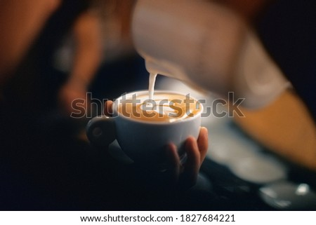 Professional barista pouring latte foame over coffee, espresso and creating a perfect cappuccino Stok fotoğraf ©