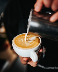 Professional barista pours white milk latte foam into a cup of coffee - the art of brewing excellent cappuccino
