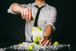 Professional barman squeezing lime with hand while making Mojito cocktail