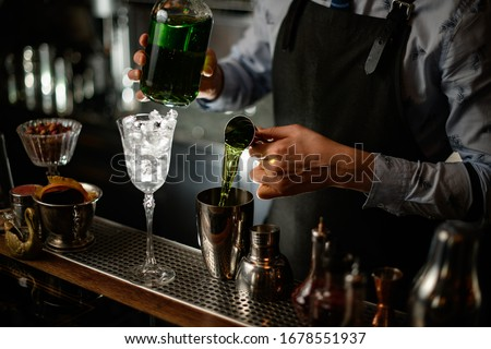 Professional barman using beaker pours green alcoholic drink into shaker with one hand and holds bottle in other.