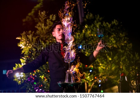 Photo of Professional bartender is making flaming lamborghini cocktail at night party.