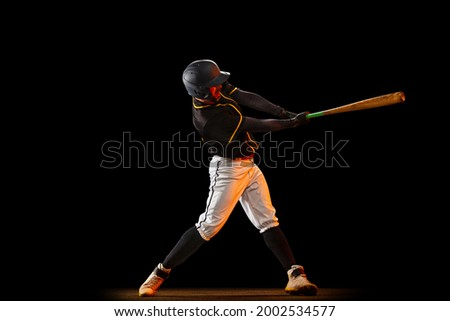Professional baseball player, pitcher in sports uniform and equipment playing baseball isolated on black studio background in neon light. Competition, show and team sport concept. Copy space for ad. ストックフォト ©