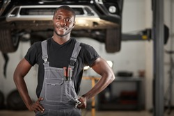 professional black auto mechanic looking at camera, handsome black guy in uniform is keen on repairing car. automobile in the background