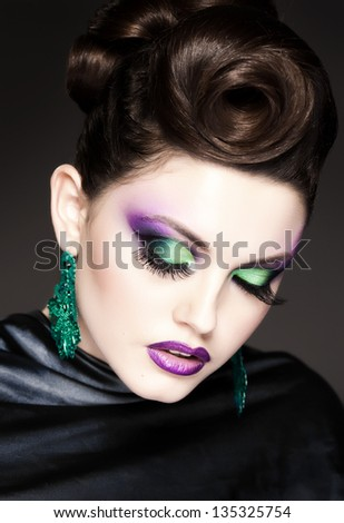 professional blue make-up and hairstyle on beautiful woman face - studio beauty shot