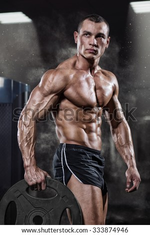 Professional bodybuilder with weight disk in gym. Weightlifter with naked torso and the disk in the hands. Fitness male model