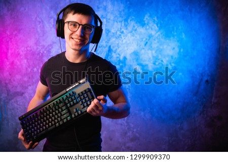 Professional Boy Gamer holding gaming keyboard over colorful pink and blue neon lit wall. Gaming gamers concept