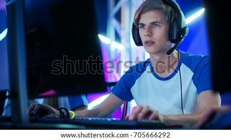 Professional Boy Gamer Plays in Video Game on a eSports Tournament/ in Internet Cafe. He Wears  Headphones and Speaks Commands into Microphone.