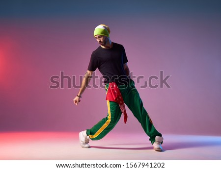 Professional breakdancer in motion on studio stage, performing energetic dance, looking down, exercising with strength to win on competition ストックフォト ©