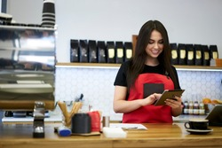 Professional brunette woman barista checking application notification on touchpad standing at bar in coffee shop, positive female manager of cafeteria using modern digital tablet for checking incomes