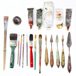 professional brushes with a palette knife and tubes of paint isolated on a white background