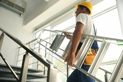 Professional builder carrying metal ladder up stairs, low angle view