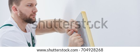 Professional builder plastering wall with plastering float