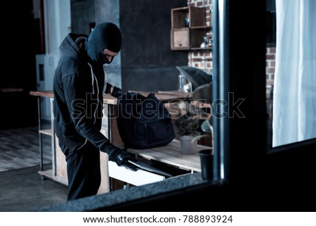 Professional burglar. Violent professional masked burglar wearing a black uniform and gloves and stealing a laptop from the table and holding a bag Сток-фото ©