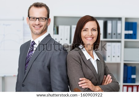 Professional Business Man And Woman Standing Back To Back In The Office Looking At The Camera With Confident Smiles At The Success Of Their Partnership
