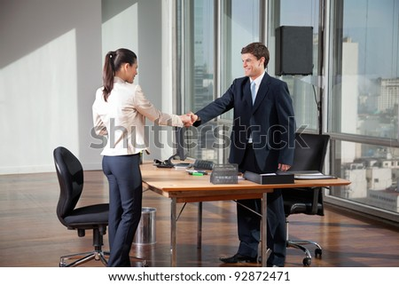 Professional business people shaking hands over a deal in office