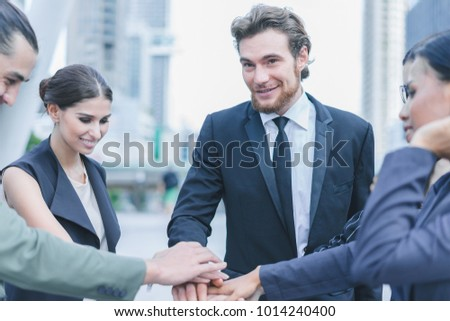 Professional business team joining stack hands and show hands together corporate meeting teamwork in cityscape background, business people concept