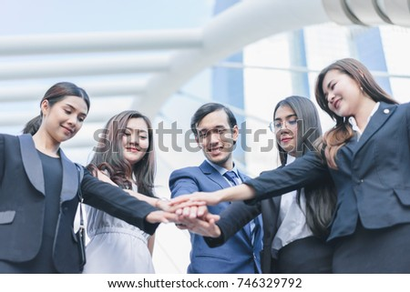 Professional business team joining stack hands and show hands together corporate meeting teamwork in cityscape background, business people concept - Shutterstock ID 746329792