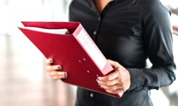 Professional business woman holding folder full of paper documents. Lawyer, legal adviser, office assistant or company manager with binder.